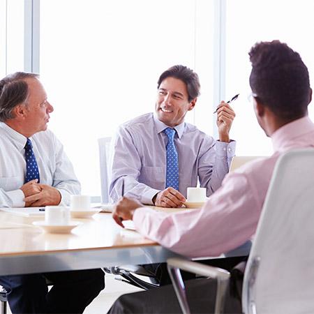 four-businessmen-having-meeting-around-boardroom-P3UA2QA